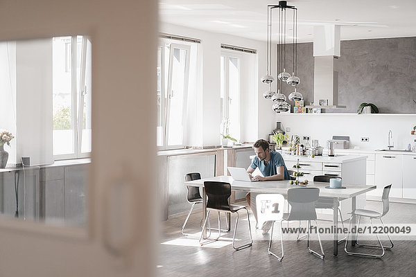 Man sitting at table in the kitchen working on laptop