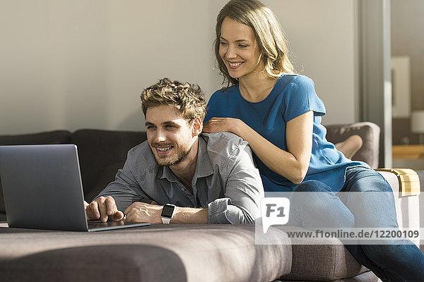 Lächelndes Paar mit Laptop auf dem Sofa zu Hause