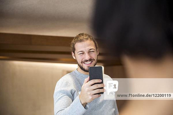 Porträt eines lächelnden Mannes  der seine Freundin fotografiert.