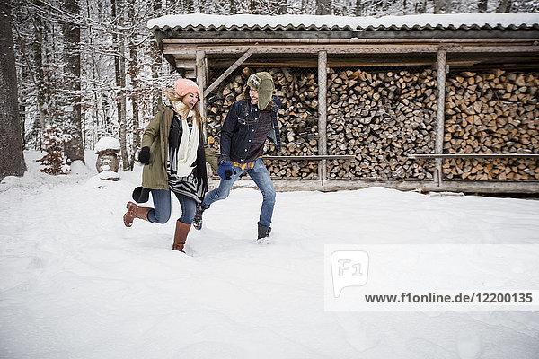 Glückliches Paar  das im Winter vor einem Holzhaufen im Freien läuft.