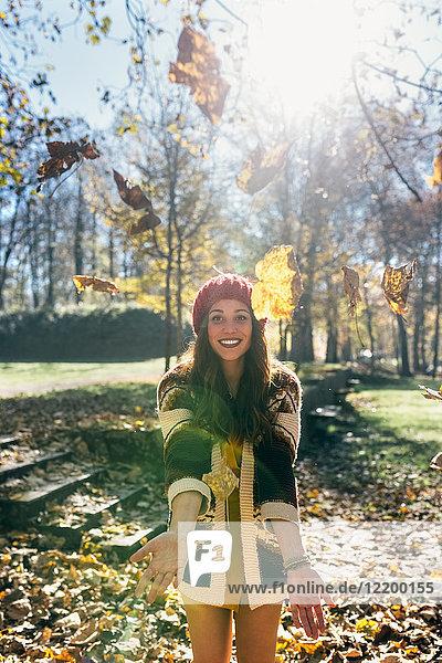 Porträt einer schönen  fröhlichen Frau  die sich mit Blättern in einem herbstlichen Wald amüsiert.