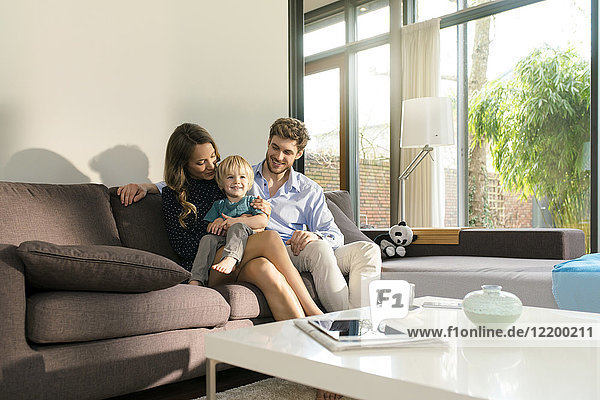 Smiling parents and son sitting on sofa at home