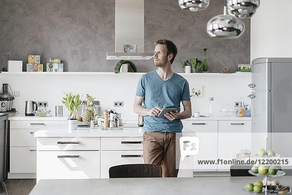 Mann mit Tablette steht in der Küche und schaut in die Ferne.