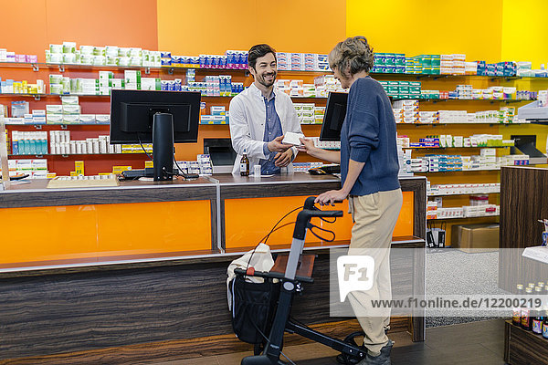 Pharmacist giving medicine to customer with wheeled walker in pharmacy