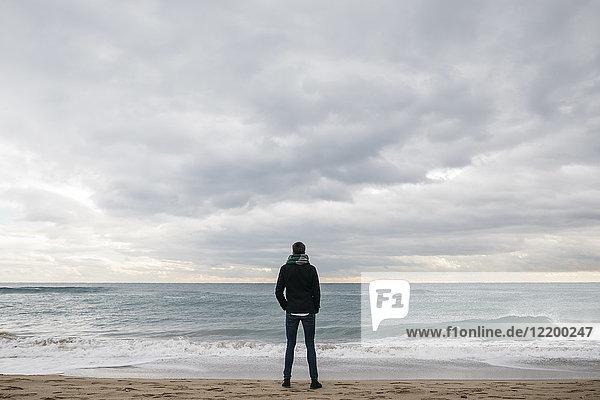 Rückansicht des Mannes  der im Winter am Strand steht und in die Ferne schaut.