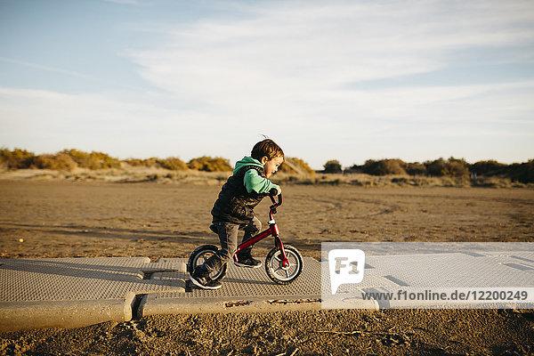 Junge läuft mit dem Fahrrad am Strand im Winter