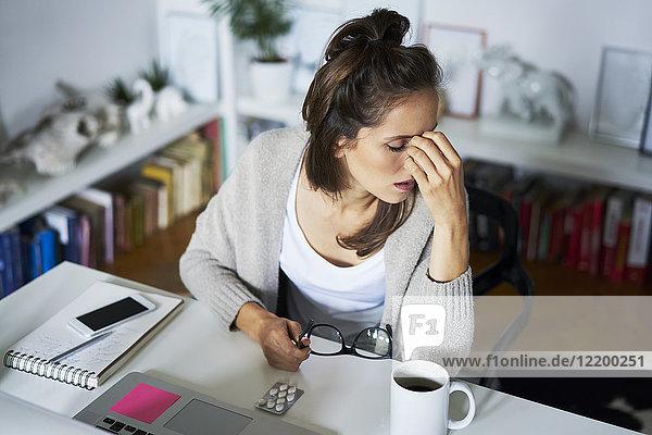 Junge Frau zu Hause am Schreibtisch mit Kopfschmerzen