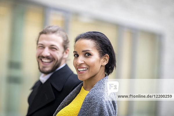 Porträt einer lachenden jungen Frau mit ihrem Partner im Hintergrund