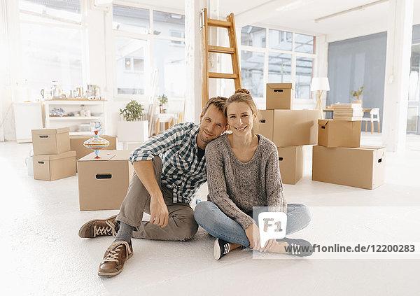 Porträt eines lächelnden Paares beim Einzug in ein neues Zuhause
