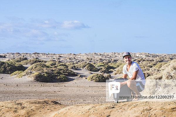 Glücklicher Mann mit Rollkoffer in Dünenlandschaft