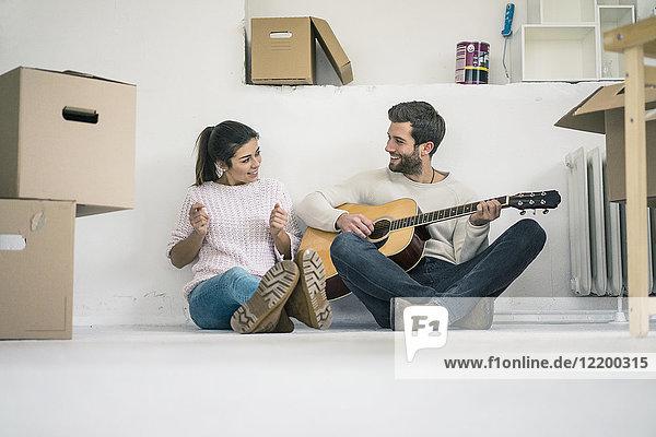 Ein Paar sitzt auf dem Boden und spielt Gitarre.