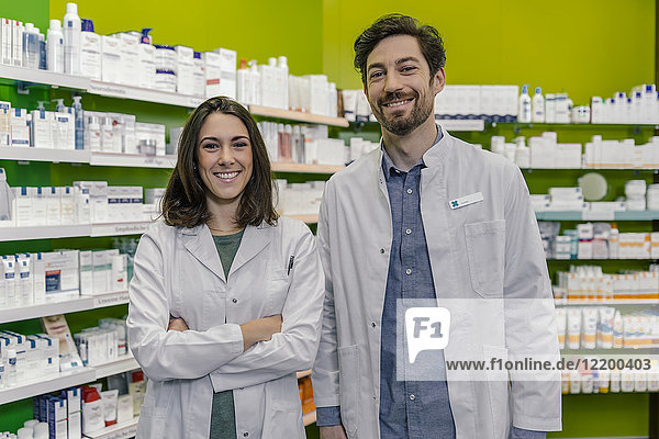 Porträt zweier lächelnder Apotheker im Regal mit Medikamenten in der Apotheke