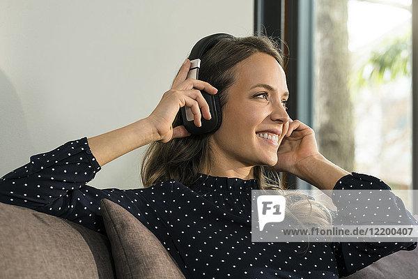 Lächelnde Frau mit Kopfhörern entspannt auf der Couch zu Hause
