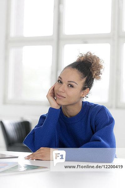 Porträt einer lächelnden jungen Frau  die am Tisch sitzt.