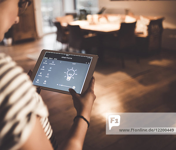 Frau mit Tablett mit Smart Home Control Funktionen zu Hause