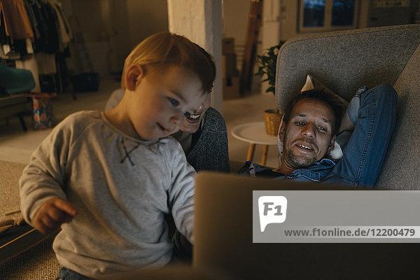 Familie betrachtet Laptop auf der Couch im Dunkeln