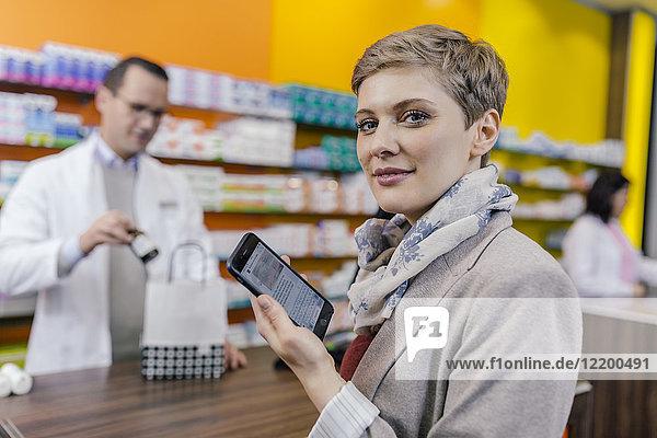 Porträt einer Frau mit Handy am Schalter in der Apotheke