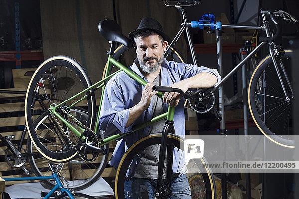 Porträt eines selbstbewussten Mannes in der Werkstatt mit Fahrrad