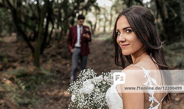 Porträt der lächelnden Braut mit Blumenstrauß im Wald mit Bräutigam im Hintergrund