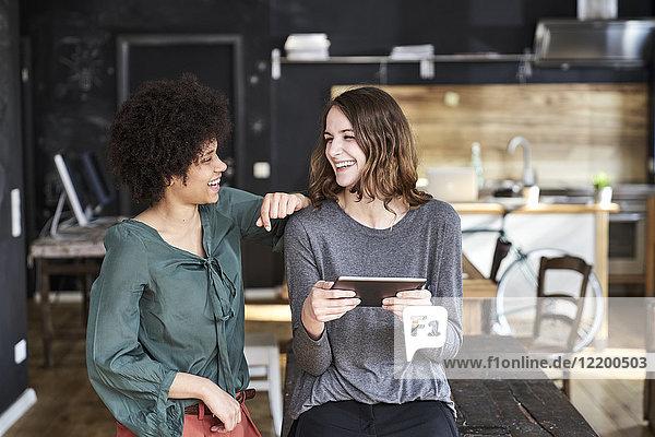 Zwei lachende junge Frauen mit Tablette im Büro