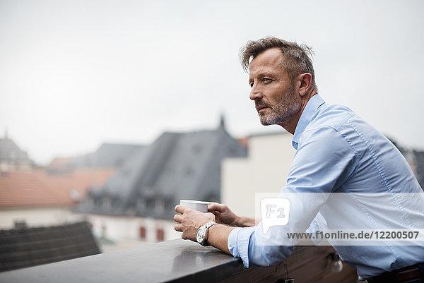 Porträt eines reifen Geschäftsmannes mit Tasse Kaffee auf der Dachterrasse