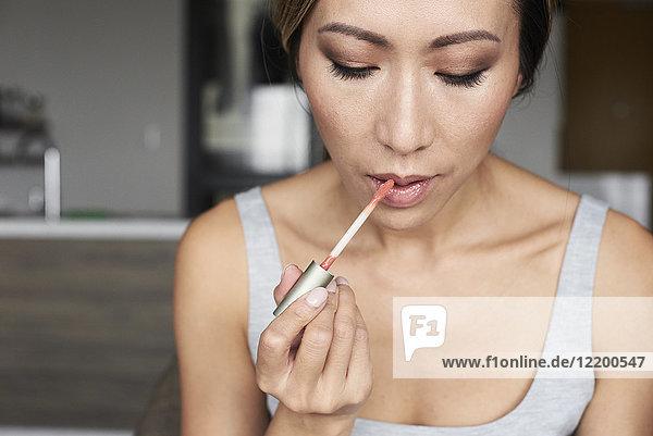 Frau zu Hause mit Make-up und Lip Gloss