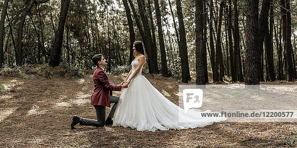 Man kneeling making a marriage proposal to happy bride in forest