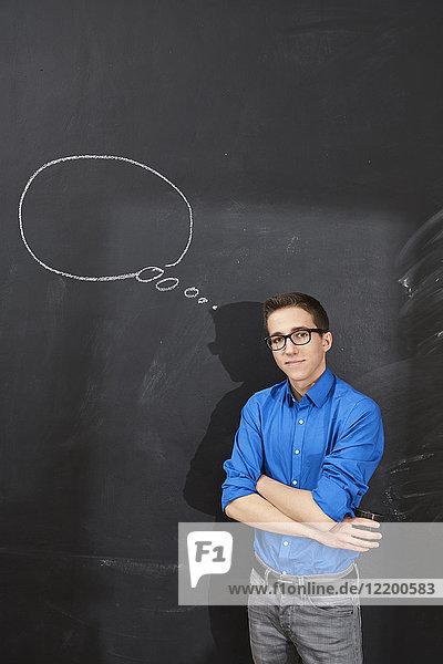 Porträt eines selbstbewussten jungen Mannes an der Tafel mit Gedankenblase