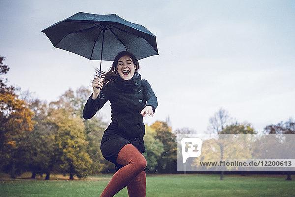 Porträt einer fröhlichen jungen Frau mit Regenschirm im herbstlichen Park