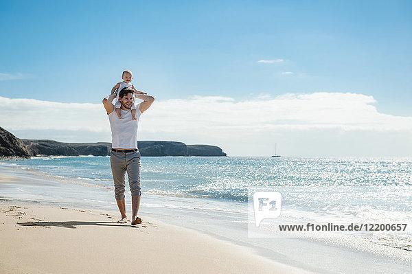 Spanien  Lanzarote  Vater mit kleiner Tochter auf den Schultern am Strand