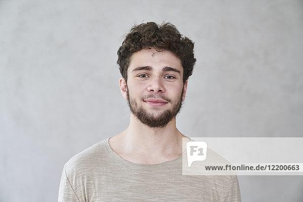 Porträt eines lächelnden jungen Mannes vor grauer Wand