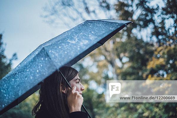 Junge Frau mit nassem Regenschirm im Herbstpark