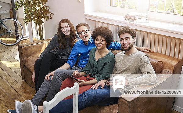 Porträt von lächelnden Jugendlichen auf dem Sofa mit Tablette