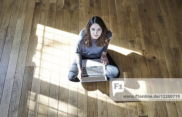 Portrait einer jungen Frau mit Laptop auf Holzboden