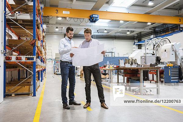 Zwei Männer in der Fabrik sehen sich den Plan an.