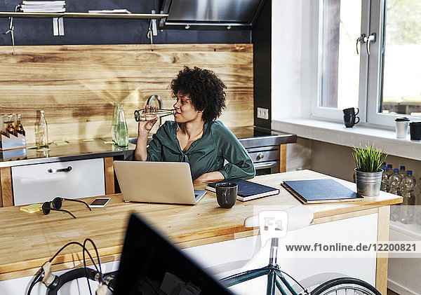 Young woman using laptop on kitchen counter