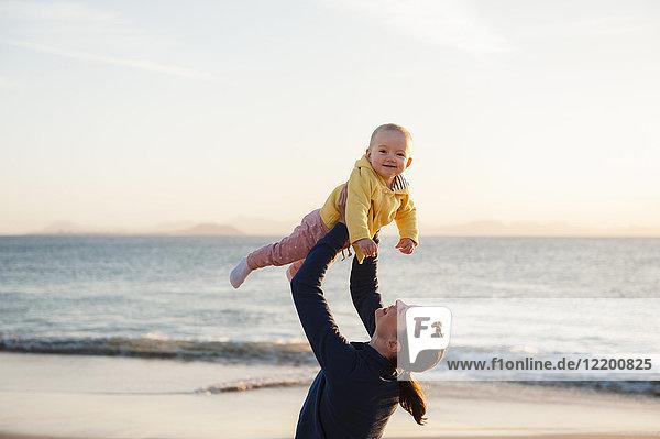 Mutter hebt kleine Tochter am Strand auf