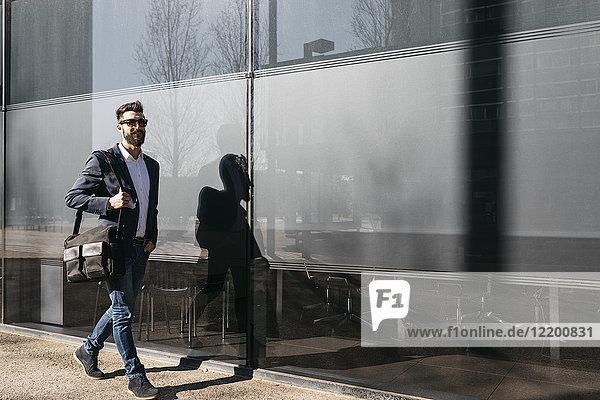 Geschäftsmann mit Sonnenbrille  der am Gebäude entlang läuft.