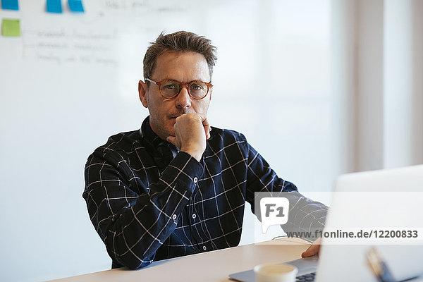 Porträt eines seriösen Geschäftsmannes mit Laptop am Schreibtisch im Büro