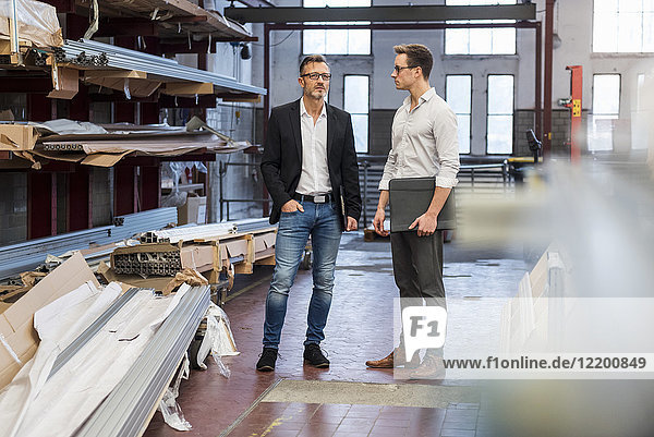 Two businessmen standing in factory storeroom