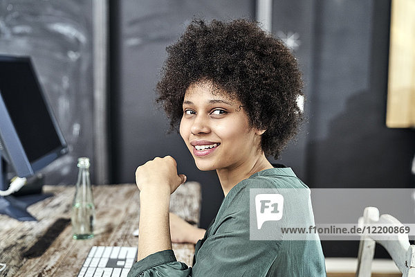 Porträt der lächelnden jungen Frau am Holztisch im Büro