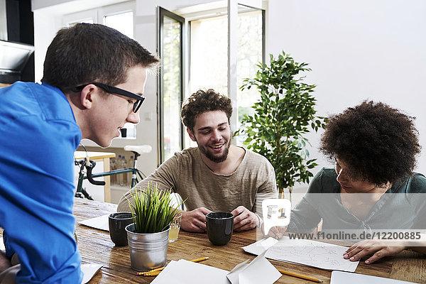 Mitarbeiter arbeiten zusammen und machen sich Notizen am Tisch im Büro.