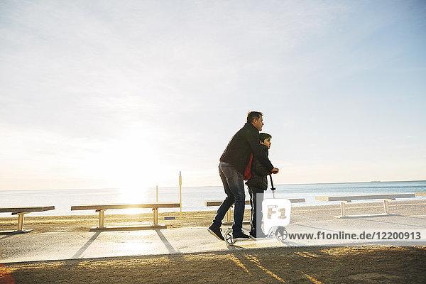 Vater und Sohn fahren Roller auf der Strandpromenade bei Sonnenuntergang