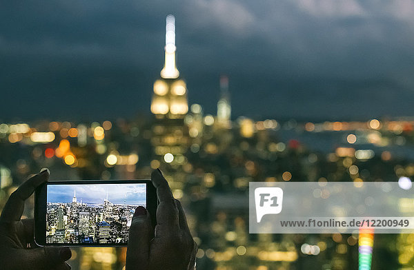 USA  woman hands holding smartphone while taking a photo of Manhattan at night