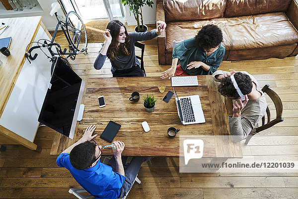 Elevated view of coworkers listening to music at wooden table in office