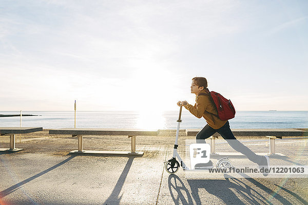 Junge fährt Roller an der Strandpromenade bei Sonnenuntergang