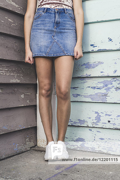 Junge Frau in einer Ecke stehend mit Jeansrock  Teilansicht
