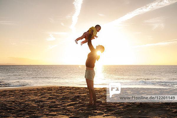 Mutter hebt kleine Tochter am Strand bei Sonnenuntergang auf.