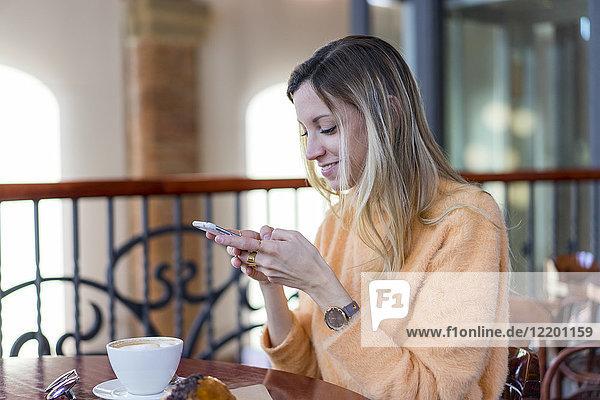 Lächelnde junge Frau in einem Café mit Handy