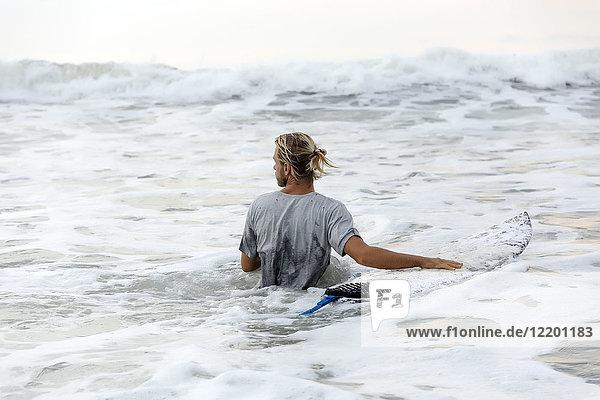 Indonesien  Bali  Surfer und Surfbrett im Wasser